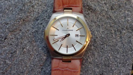 Jacques Lemans man QUARTZ Watch    Silver decorated dial with golden markers and Hands    Date window yes at 3 oclock    Water Resistant yes    Sapphire Crystal  Swiss QUARTZ Movement marked. NEW BATTERY.    Comes with original light brown worn leather band.  Last serviced 10.2012  Subjective : A touch of LUXURY for the fraction of the price. What do YOU think?