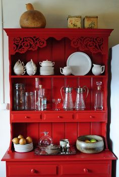 Classic white and glass dishes pop off this bright red hutch.