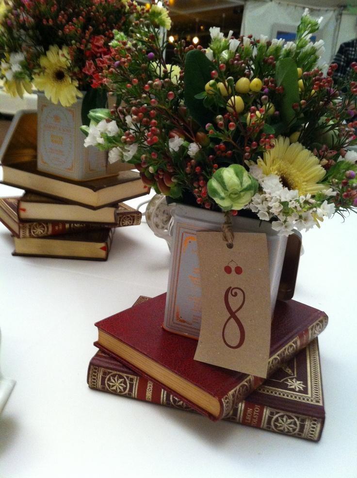 Shabby Chic. Libros vintage apilados, latas de té de estética vintage y flores silvestres para esta mesa tan especial.