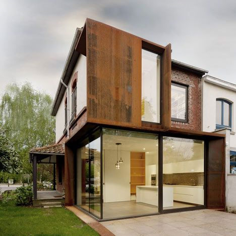 Exar Architecture, you can see the heritage home in brick along the ends, but the corten steel is a good match to the rustic traditional house.