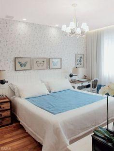 Neste quarto em um apartamento em Copacabana, no lugar de uma cabeceira convencional, é o lambri branco que emoldura a cama e oferece o arremate para o papel de parede estampado de azul e branco (Covering). O visual é de praia romântica, como a moradora queria. Quadros de borboletas da Toute Chose e colcha da Brasil Interiores. Reforma da L+O Arquitetos Associados.