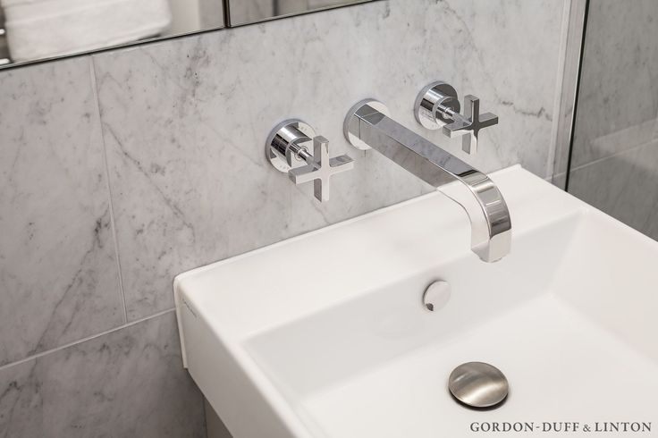 Carrara marble tiles and Hansgrohe wall mounted taps in bathroom.