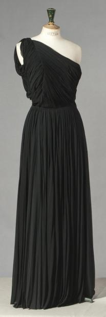 GRES, 1 rue de la Paix, haute couture, circa 1947/1950  Evening dress in black silk jersey, draped top with asymmetrical neckline, falling lightly on the shoulder, very full skirt with gathered waist