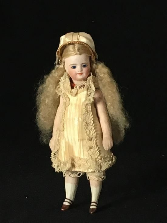 """5 1/2"""" ANTIQUE ALL BISQUE MIGNONNETTE.  LONG MOHAIR WIG ON CORK PATE, GLASS SLEEP EYES, CLOSED MOUTH, ON ON 5-PIECE PEG JOINTED BODY WITH MOLDED AND PAINTED 2-STRAP SHOES AND STOCKINGS. ANTIQUE COSTUME."""