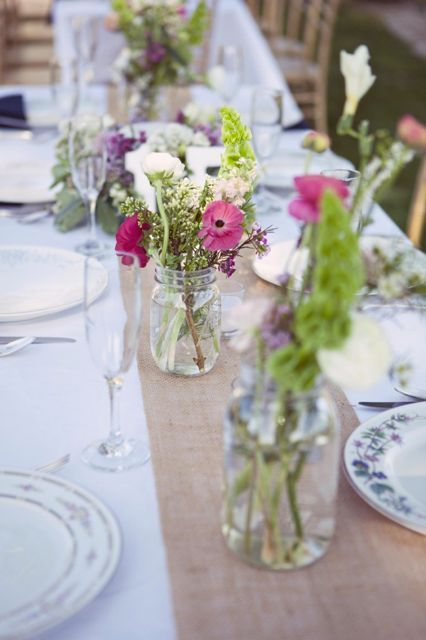 Simple and very thrifty tablescape. Flowers in glass jars.