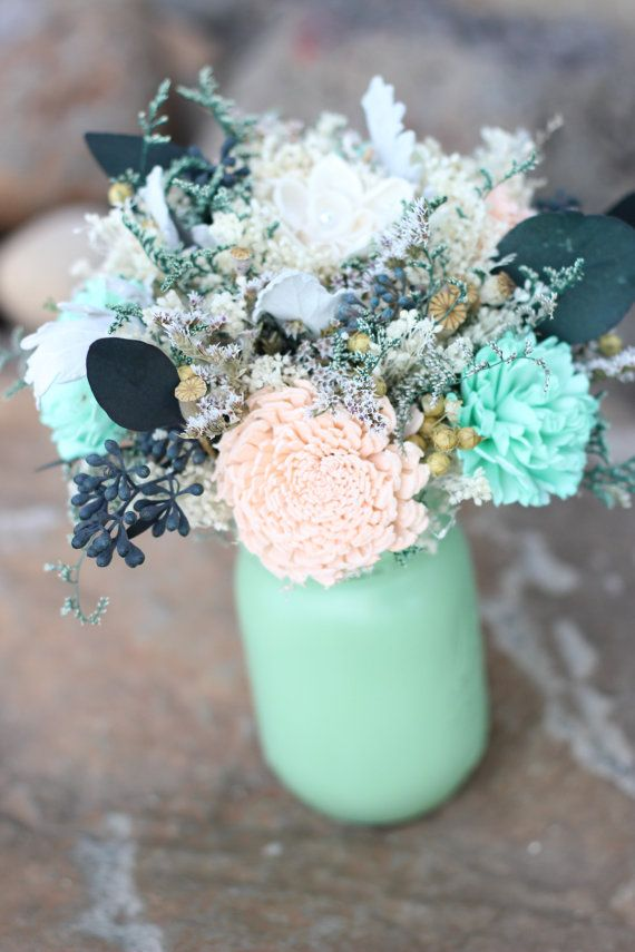 This beautiful centerpiece features sola flowers in peach and mint and premium fillers such as seeded eucalyptus, white german statice, poppy pods, ivory baby's breath, green caspia and silver dusty miller.