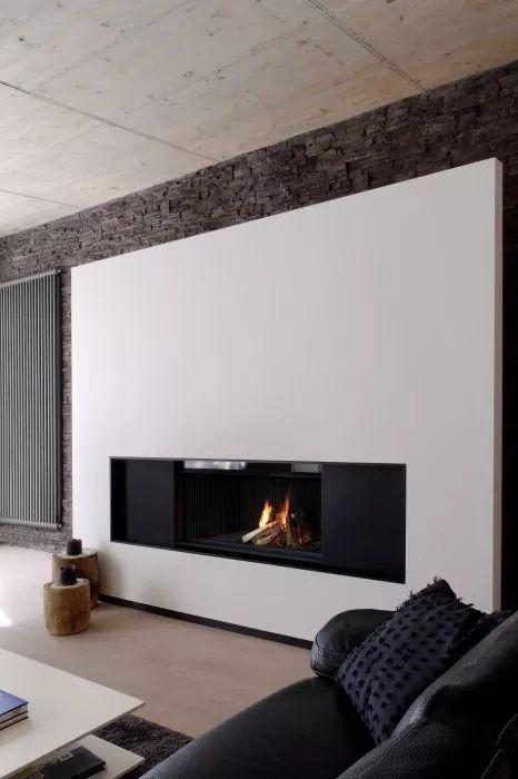 Idea camino moderno a legna su grande parete bianca davanti ad un muro in pietra naturale e rustico. Camino in metallo nero