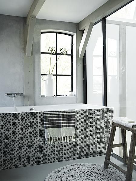 Black and white bathroom with bath, knitted carpet and wooden stool