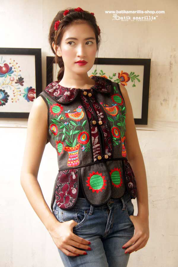 http://batikamarillis-shop.com Batik Amarillis made in Indonesia  batik amarillis's piccola vest  features Ukrainian embroidery inspired meets tenun batik  gedog Tuban,Indonesia. Take a fresh, sweet & whimsical approach to power dressing with this Krakow-Poland classic traditional folklore inspired jacket.  The beauty essential is reworked with a contrast-coloured batiks,unique cuttings ,trims,glossy beaded buttons,it has fitted waist with unique peplum petals