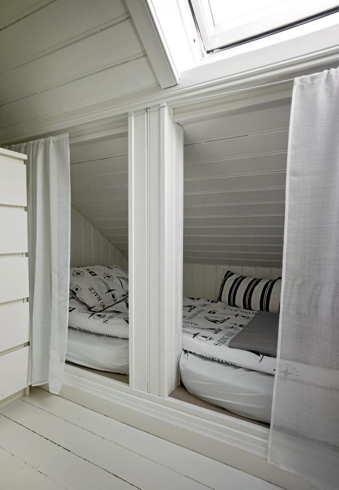 På dette loftet er plassen utnyttet maksimalt. Under skråtaket er det laget en liten soveplass som enkelt kan skjules ved å trekke for de hvite gardinene.