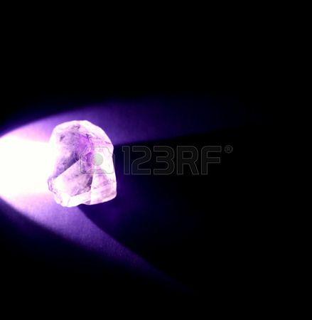 Illuminated amethyst on purple background with black negative space