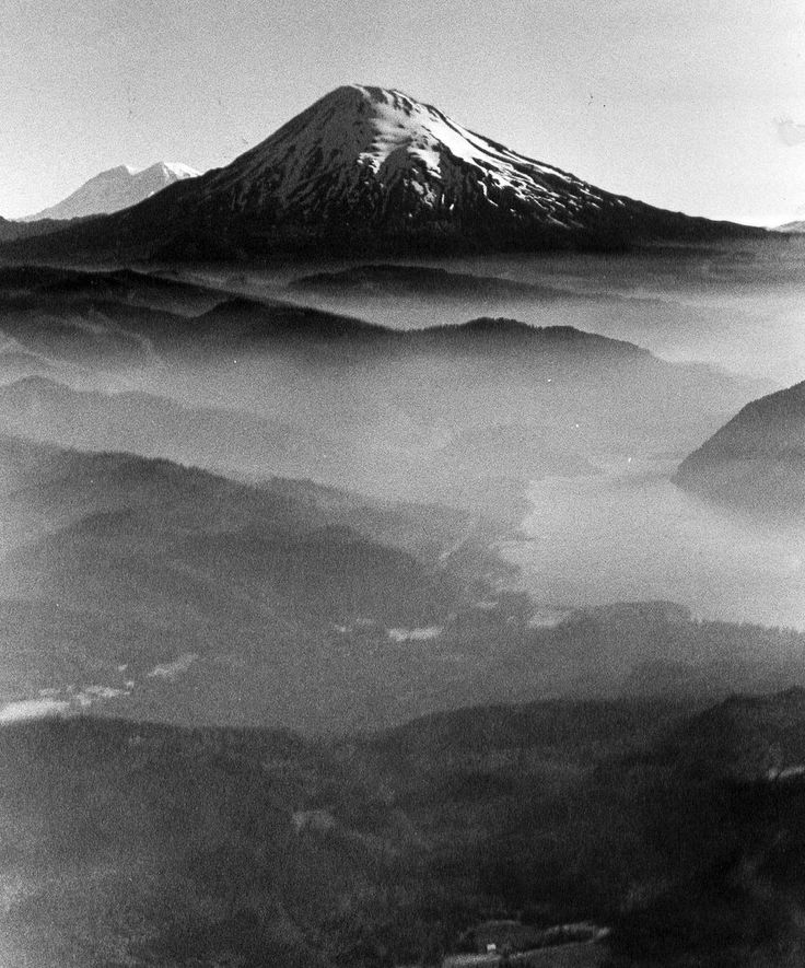 March 27, 1980 - Mount St. Helens takes on summer sun above haze that hovers over forests and Yale Reservoir. Peeking over the mountain's shoulder is Northwest's biggest, Mount Rainier. Wes Guderian/The Oregonian