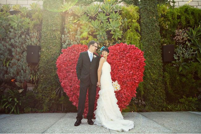 A red floral heart makes for a dramatic ceremony backdrop.    Image via  Ashley Rose .