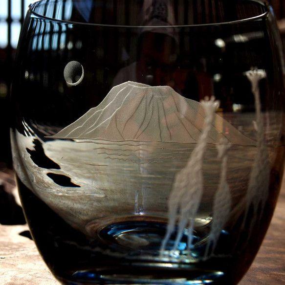 ポーランド製のロックグラスを使用しています。表面には、、恐らく、、低温(200℃くらい)で溶けるエナメル釉彩を施していると思われ、、表面を彫刻するとスリガラスとエナメル釉彩色との対比が美しいです。この釉彩の色を活かして夜のタンザニアの風景を彫刻しました。グラスの手前には網目キリンの親子。グラスの向こう側にはキリマンジャロと三日月。アフリカを想いながら飲むのはいかがでしょうか。最後の画像はペアのイメージです。※名入れ可能です。(詳しくは『名入れ始めました』をご覧ください)※ギフト用に別売り(800円)の化粧箱あり通常は折りたたみ式のボール箱に入れて発送しますプレゼント・ご自分用に高さ8.5cm  口径8cm