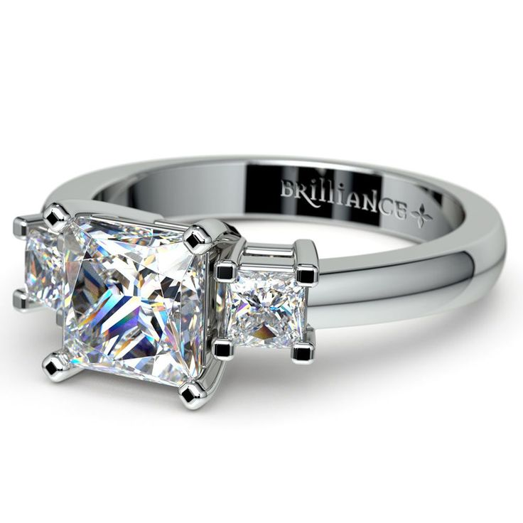 A classic three stone design in white gold, this ring features two Princess Forever Brilliant Moissanite stones alongside a larger 5.5 mm Princess Forever Brilliant Moissanite in a basket style setting.