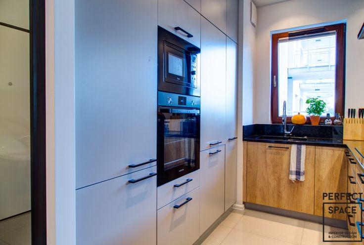 Wnętrze nowoczesnego aneksu kuchennego z jasnymi frontami szafek i czarnym blatem. Sprzęty ADG w zabudowie.