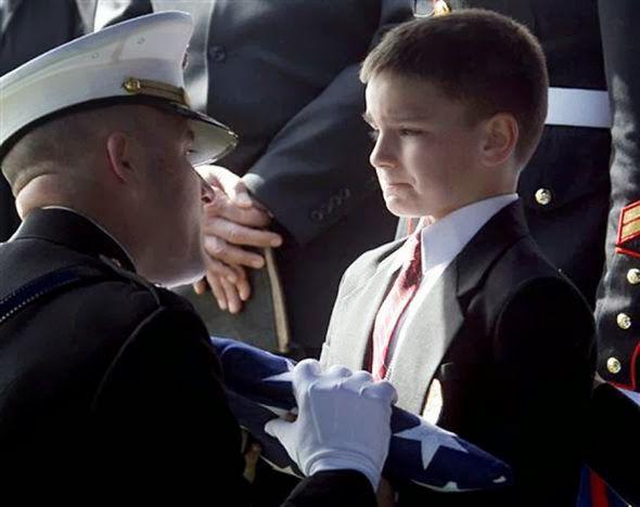 Christian de 8 años recibe la bandera estadounidense durante una ceremonia en memoria de su padre, muerto en Irak semanas antes.