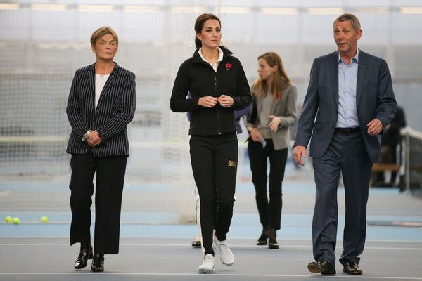 Kate Middleton Photos - Catherine, Duchess of Cambridge, walks with the President of the LTA, Martin Corrie (R), and LTA Director of Human Resources Vicky Williams (L) during a visit at the Lawn Tennis Association (LTA) at the National Tennis Centre on October 31, 2017 in southwest London, England. The Duchess of Cambridge, who became Patron of the LTA in December 2016, visited the LTA, the national governing body of tennis in Great Britain, where she was briefed on the organisations latest…