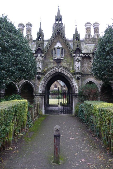 "Holly Village Highgate, London The main entrance to this model village of eight houses commissioned by Lady Burdett Coutts who lived in a splendid house close by. The family's diamond-shaped coat-of-arms is carved prominently in Portland stone on each building, and over the entrance arch is engraved, ""Holly Village Erected By A. G. B. Coutts A.D. 1865."""