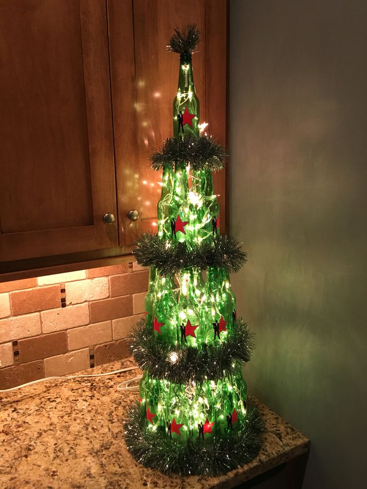 Heineken/Beer Christmas Tree. One case of beer, two strands of icicle lights, foam poster board, and glass epoxy. Fun Christmas bar decor!