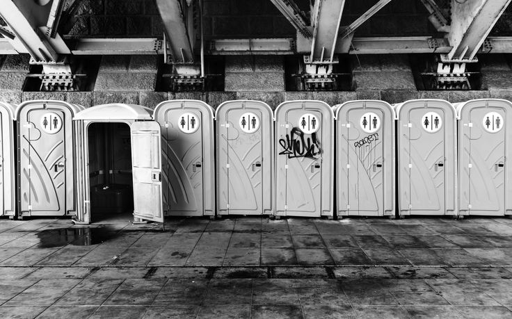 Under the bridge - Row of plastic portable toilets under the bridge. One is different in shape and opened