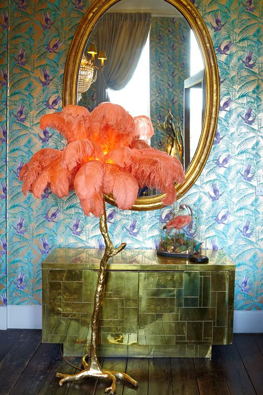 Orange feathers on a tree-like gold lamp stand by 'A Modern Grand Tour'. Inside the bridal suite designed by Matthew Williamson at Aynhoe Park - gold drawers and mirror pop against Osborne and Little metallic songbird blue and purple wallpaper.