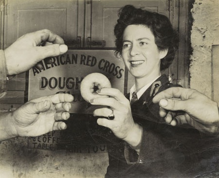 """Elizabeth Williams holds a doughnut out to the hands of flyers returning from bombing runs at an American Red Cross clubmobile in southern Italy in 1943. The photo is a classic depiction of a Red Cross """"Doughnut Dolly."""""""