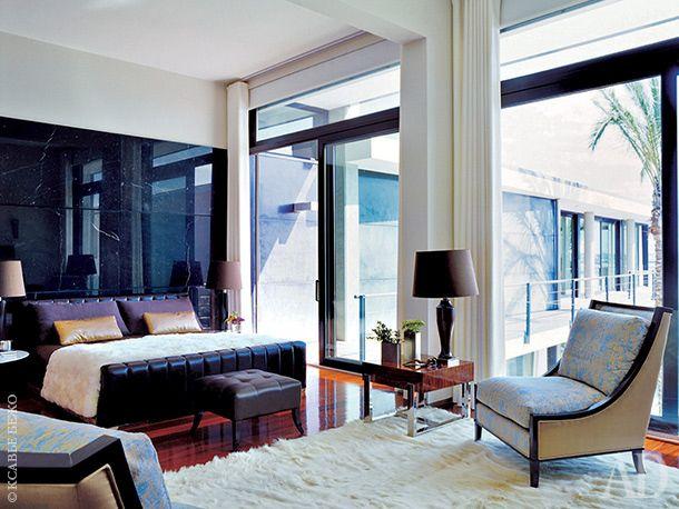 Спальня хозяев: черный мрамор на стене и белый мех на полу.