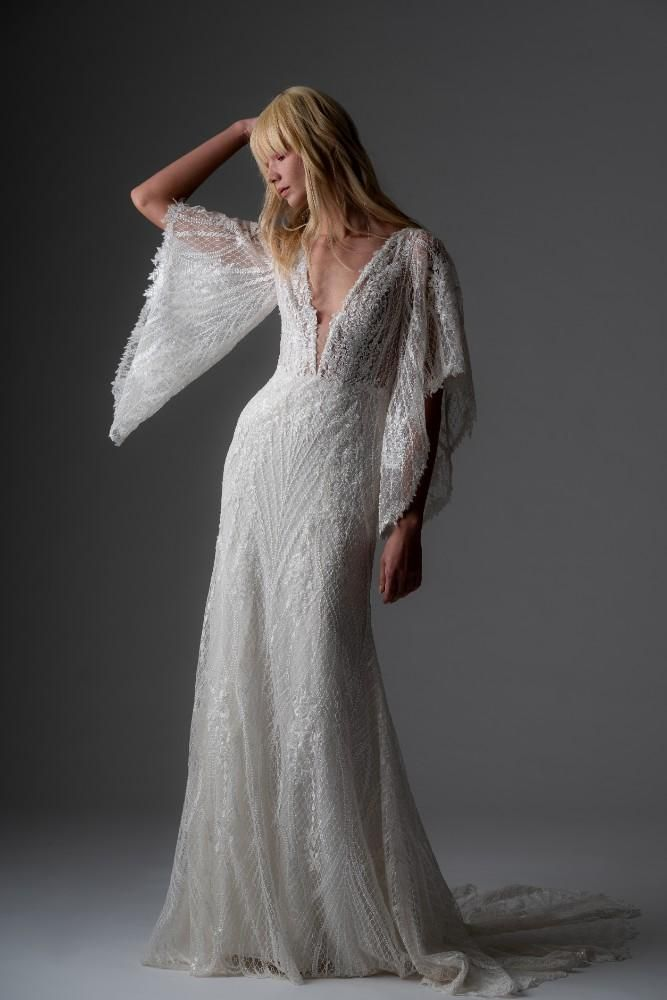 031c88ec78f54 The Greer is a lace wedding dress featuring long sleeves and a deep-V  neckline. The sheath wedding gown has butterfly sleeves.