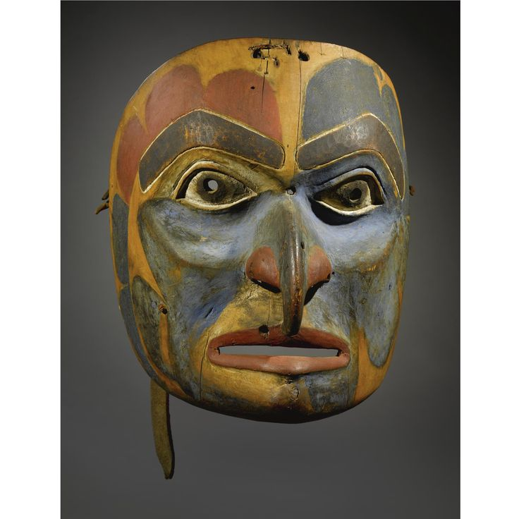 """A BELLA COOLA POLYCHROMED WOOD MASK    composed of carved wood, hideand pigments, depicting a hawk; the back secured with a wooden """"bite.""""  Height 11 in."""