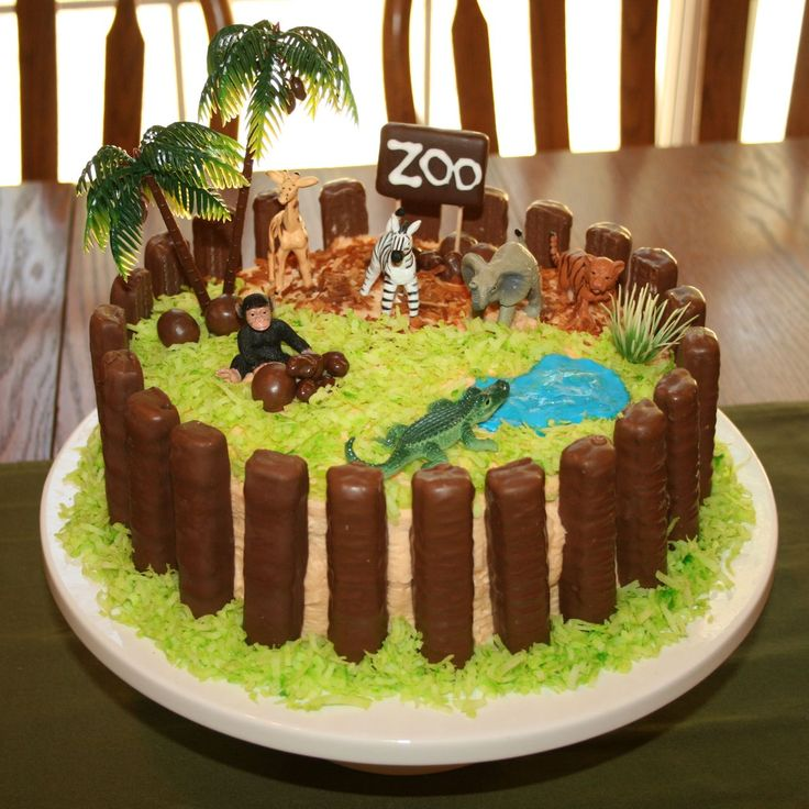 "Zoo birthday cake - Zoo Cake Supplies:  2 - 9"" round cakes, Shredded Coconut - Some tinted Green and Some Toasted Blue Gel Icing for Pond Twix Candy Bars  - I bought 6 king sized Twix bars. 1 Keebler Deluxe Graham, White Icing to write Zoo, and two toothpicks (Poke toothpicks into one side of cookie and stand into cake)  Some Chocolate Covered Raisins and a few Whoppers for ""rocks""  Toy Tree and Baby Zoo Animals Toob"