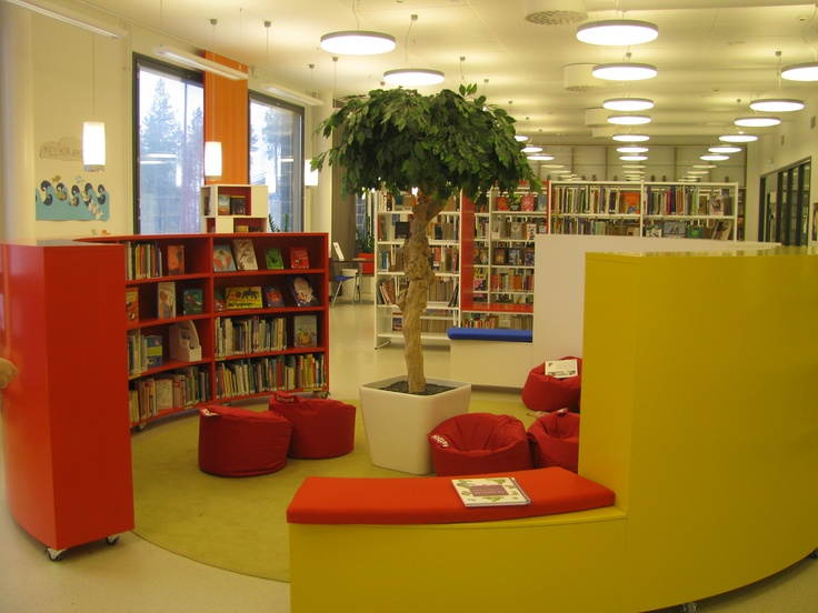 Ritaharju School, Oulu. Joint school and public library; reading nook demarcated by colourful circular fiction shelves; colours denote reading levels. Note lighting, light floor and walls with harmonious colour design and plants.