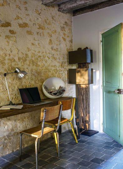 La porte de l'entrée reste dans son jus, les pierres apparentes donnent du cachet à la pièce, relevé par un sol en pierre bleue du Vietnam - Plus de photos sur Côté Maison http://petitlien.fr/79u0