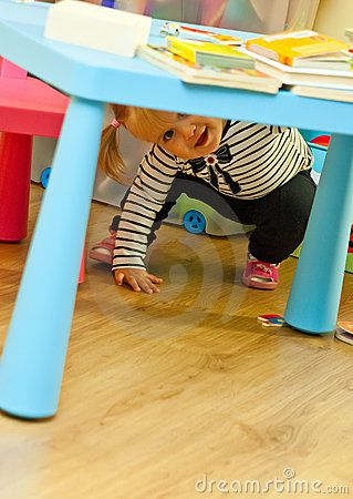 Cute preschool girl playing under plastic table with books on top.