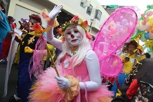 Not waving but clowning - a winged participant takes to the streets