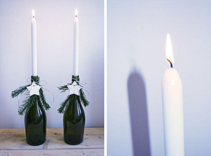 DIY kerstdecoratie lege wijnfles kaarsen - gezien: i.p.v. dennentakjes een klimoprank om de fles heen wikkelen. Vastgezet met groenijzerdraad. Super eenvoudig en toch sierlijk!