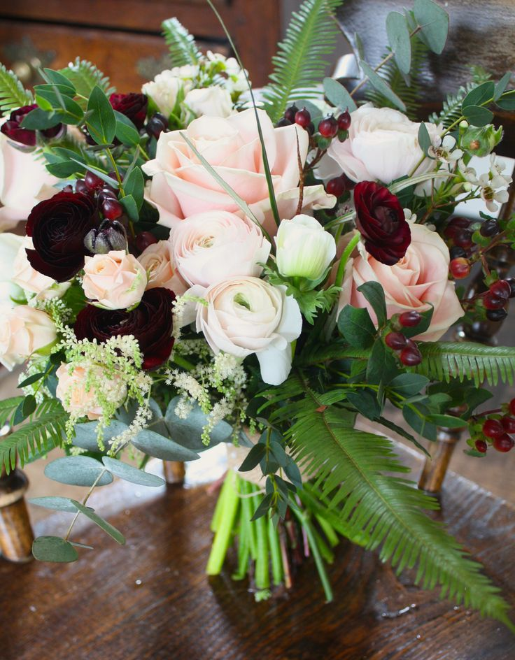 Natural foliage blush pink roses burgundy ranunculus bridesmaids bouquet.
