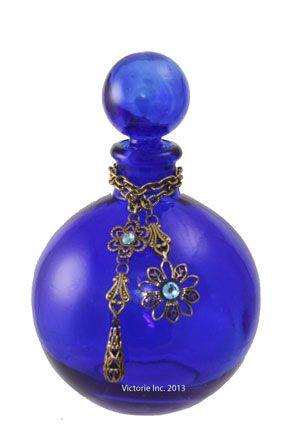 Stunning cobalt blue glass bottle with ground glass stopper.  Adorned with vintage gold Swarovski crystals.
