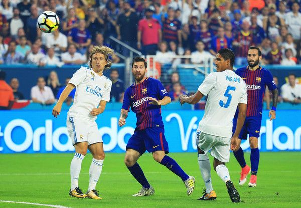 Lionel Messi #10 of Barcelona scores against the defense of Raphael Varane #5 and Luka Modric #10 of Real Madrid in the first half during their International Champions Cup 2017 match at Hard Rock Stadium on July 29, 2017 in Miami Gardens, Florida.