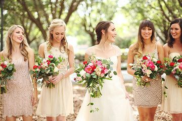 the bride heads to the ceremony along with her   bridesmaids dressed in a neutral blush dresses, carrying loose unstructured bouquets of coral charm peony, red ranunculus, Vendala roses, hot pink ranunculus, light pink lisianthus, jasmine vine, magnolia leaves, lemon leaf, peach stock, succulents & seeded eucalyptus wrapped in cream muslin ribbon.