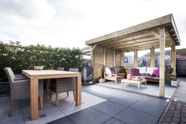 De Living modulair is naar eigen wens in te delen met diverse soorten wanden en is verkrijgbaar in verschillende afmetingen. De loungeset is gemaakt van recycled teak en staat op lichtblauwe keramische vloer omlijnd met  een donkerbruine nieuw gebakken klinker. De tuinset ervoor is gemaakt van wicker stoelen met teak tafel op kleurvaste Geosteen betontegels.