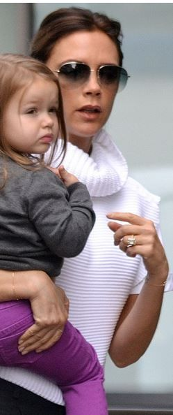 Who made  Victoria Beckham's white turtleneck sweater vest, aviator sunglasses, black capri pants, and gray handbag?