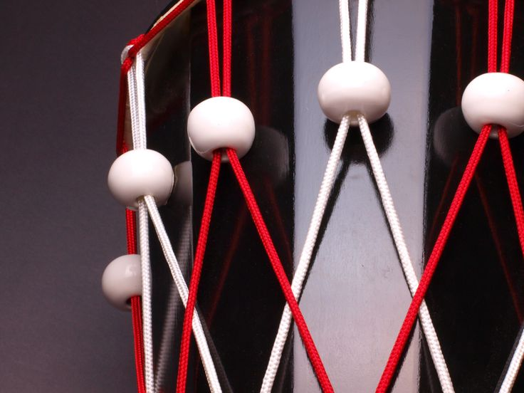 Ashiko hand drum close up, ceramic tuners, red and white polyester rope.