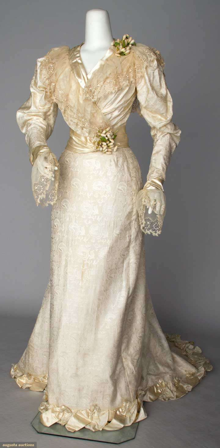 "Silk wedding gown, c1890; Cream silk damask in paisley pattern, trained skirt attached to bodice at center back, lace and self fabric bow trims, embroidered net lace collar and cuffs, wax orange blossom clusters at shoulder and waist, B 36"", W 24"", Skirt L 43""-72"""