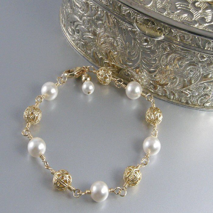 White pearl and 22k gold plate filigree bead bracelet with 14k gold filled lobster clasp.  BUY NOW http://jewelrybytali.com/products/gold-filigree-white-pearl-bracelet