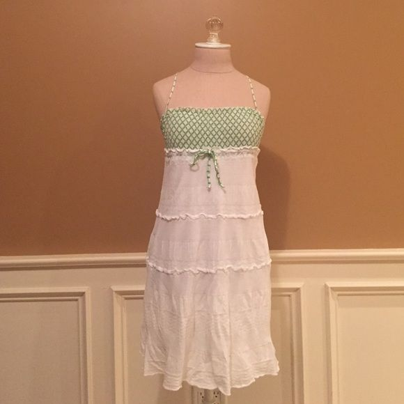 Free People Dress This cute white with green accented dress is perfect paired with sandals or flats and a jean jacket for a flirty yet casual look, or can be thrown over a bathing suit as beach wear. The loose cotton skirt and stretchy criss crossed bust area with subtle frills is flattering on any body type and a staple piece for any girls closet. Although it's a small, the stretchy fabric makes it roomy for mediums and all bust sizes Free People Dresses
