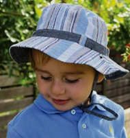 Boys Batemans Bucket - Reversible.   This very smart summer hat is made from soft 100% cotton. It is fully reversible, giving you 2 styles from one hat. One side has a blue, white, navy and tan print and the other is plain slate. The toggle adjustable chin strap attaches with press studs, which can be re-attached when the hat is reversed.