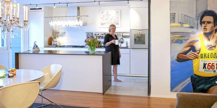 Stort maleri av Anders Kjær dominerer på den ene kjøkkenveggen. Innredning fra Bulthaup. Lampe Cullula over kjøkkenøya.
