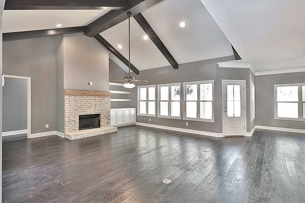 Gorgeous family room. I love grey walls, white trim & hardwood floors. This space is even more stunning with the brick fireplace, wood mantel and wood beams!!