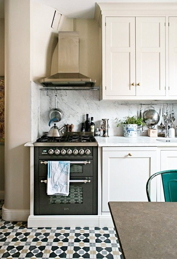 Small kitchen with marble backsplash, under cabinet storage, and geometric patterned tile floor.